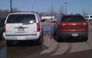 Traverse (pictured in red) parked next to a Chevy Tahoe, takes up a slightly smaller footprint