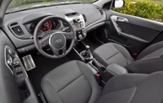 The driver faces a molded steering wheel and the dash instruments with big round analog gauges including a tachometer